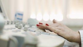 Kvinnliga doktorns hand som förbereder en ultraljudapparatbildläsning, steadicam sköt, närbilden arkivfilmer