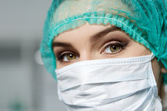 Kvinnliga doktors framsida som bär den skyddande maskeringen Arkivbild