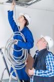 Kvinnliga eleectrician sättande rör i tak arkivfoto
