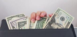 Kvinnliga fingrar på en grupp av amerikanska dollarräkningar arkivfoto