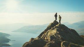 Kvinnliga fotvandrare överst av berget som tar ett avbrott och tycker om en dalsikt Arkivbilder