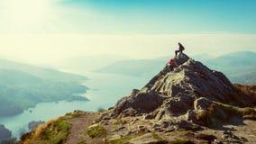 Kvinnliga fotvandrare överst av berget som tar ett avbrott och tycker om en dalsikt Royaltyfria Bilder