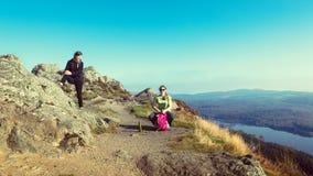 Kvinnliga fotvandrare överst av berget som tar ett avbrott och tycker om en dalsikt Arkivbild