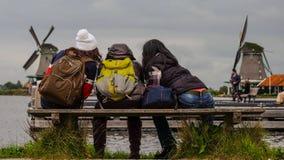 Kvinnliga fotvandrare framme av traditionella holländska väderkvarnar Royaltyfri Bild