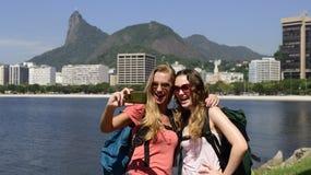 Kvinnliga fotvandrareturister med smartphonen i Rio de Janeiro med Kristus Förlossare i bakgrund. Arkivbilder