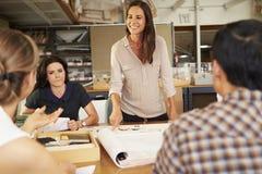 Kvinnliga framstickandeLeading Meeting Of arkitekter som sitter på tabellen Royaltyfri Bild