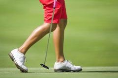 Kvinnliga golfare som går på gräsplan Fotografering för Bildbyråer
