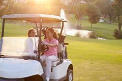 Kvinnliga golfare som kör barnvagnen längs farled av golfbanan arkivfoton
