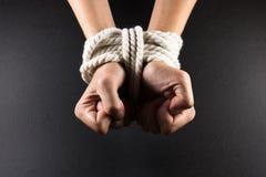 Kvinnliga händer begränsar i träldom med repet