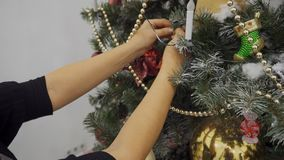 Kvinnliga händer dekorerar den konstgjorda julgranen med ljusa leksaker stock video