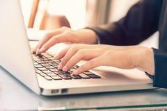 Kvinnliga händer för affärskvinna på bärbar datortangentbordet med varmt ljus c Arkivfoto