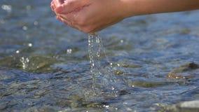 Kvinnliga händer för kvinna som utomhus griper och lyfter kristallklar sötvatten i bergfloden, droppar in i vattenyttersida stock video