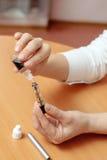 Kvinnliga händer fyller med flytande i den elektroniska cigen för clearomizers Royaltyfria Bilder