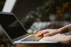 Kvinnliga händer genom att använda bärbara datorn i modernt kontor royaltyfri fotografi