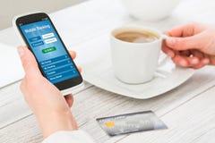 Kvinnliga händer genom att använda mobila bankrörelsen på den smarta telefonen arkivfoto