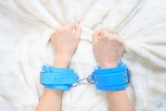 Kvinnliga händer i blåttläderhandbojor eagerly royaltyfri bild