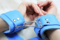 Kvinnliga händer i blåttläderhandbojor eagerly arkivfoto