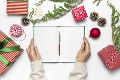Kvinnliga händer i stucken tröja skriver med pennan i rena anteckningsbokplan för det nya året, gåvaaskar, granfilialer på vit t arkivfoto
