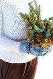 Kvinnliga händer i tumvanten med granträdfilialer i vit vinterbakgrund royaltyfria bilder