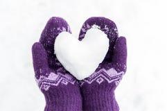 Kvinnliga händer i varma stack tumvanten håller hjärtan från snö royaltyfria foton