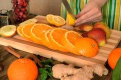 Kvinnliga händer klipper en citron i bakgrunden Royaltyfri Bild