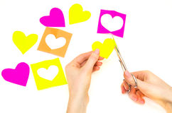 Kvinnliga händer klippta ut pappers- hjärtor Arkivfoto