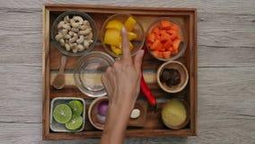 Kvinnliga händer kontrollerar ingredienser som tjänas som på magasinet som är klart att laga mat grönsaksås från morötter, kasjue arkivfilmer