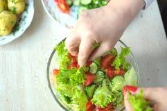 Kvinnliga händer lagar mat grönsaksallad på köket Arkivbild
