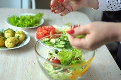 Kvinnliga händer lagar mat grönsaksallad på köket Arkivbilder