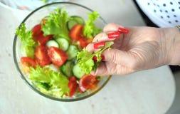 Kvinnliga händer lagar mat grönsaksallad på köket Royaltyfria Foton