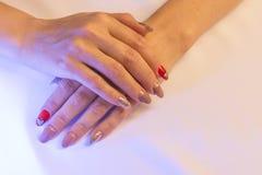Kvinnliga händer ligger överst av de och att visa en härlig handgjord konstmanikyr på en ljus tygbakgrund Hjärta royaltyfri bild
