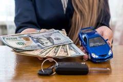 Kvinnliga händer med dollar, bilen och tangenter arkivbilder