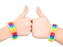 Kvinnliga händer med ett armband som mönstras som regnbågen, sjunker upp visningtummar bakgrund isolerad white Arkivbild