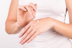 Kvinnliga händer med fransk manikyr som applicerar handkräm, vit bakgrund, closeup, främre sikt arkivbild