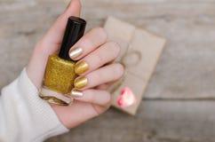 Kvinnliga händer med guld spikar design arkivbilder