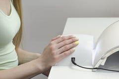 Kvinnliga händer med manikyr på UV LED spikar lampleverantören Vit b arkivfoto