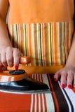 Kvinnliga händer med rött spikar och ett gammalt elektriskt järn Royaltyfria Foton