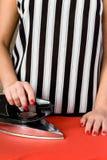 Kvinnliga händer med rött spikar och ett gammalt elektriskt järn Royaltyfri Fotografi