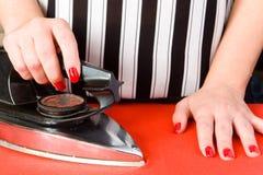 Kvinnliga händer med rött spikar och ett gammalt elektriskt järn Arkivfoton
