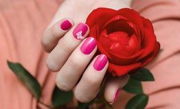 Kvinnliga händer med rosa färger spikar konst royaltyfri fotografi