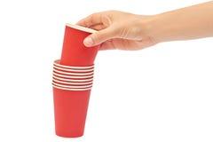 Kvinnliga händer rymmer en papp eller en plast- disponibel kopp bakgrund isolerad white Arkivfoto