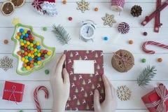 Kvinnliga händer rymmer julboken vita röda stjärnor för abstrakt för bakgrundsjul mörk för garnering modell för design royaltyfri foto