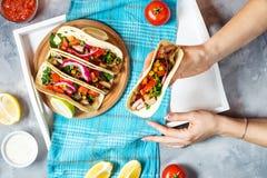 Kvinnliga händer rymmer mexikanska griskötttaco med grönsaker Tacoalpastor på träblå lantlig bakgrund överkant Royaltyfri Foto