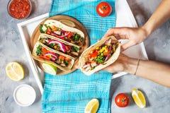 Kvinnliga händer rymmer mexikanska griskötttaco med grönsaker Tacoalpastor på träblå lantlig bakgrund överkant Royaltyfri Bild