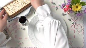 Kvinnliga händer satte matzahen på en vit platta stock video