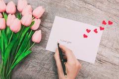 Kvinnliga händer skriver ett meddelande av förälskelse på ett vitt kuvert, på en träbakgrund valentin för dag s arkivfoto