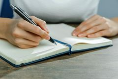 Kvinnliga händer skriver i en anteckningsbok arkivfoton