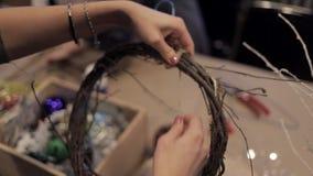 Kvinnliga händer som binder upp trästänger med, tvinnar framställning av julkransen