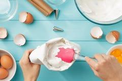 Kvinnliga händer som fyller konfektaffärpåsen med piskade äggvitor, lagar mat med grädde på blå träbackround royaltyfria foton