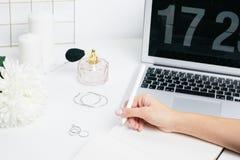 Kvinnliga händer som gör anmärkningar i en notepad på en vit tabell med ett bärbar datortangentbord arkivfoton